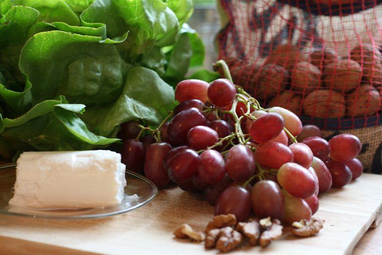 Weintrauben, Ziegenkäse, grüner Salat und Walnüsse auf einem Holzbrett arrangiert.