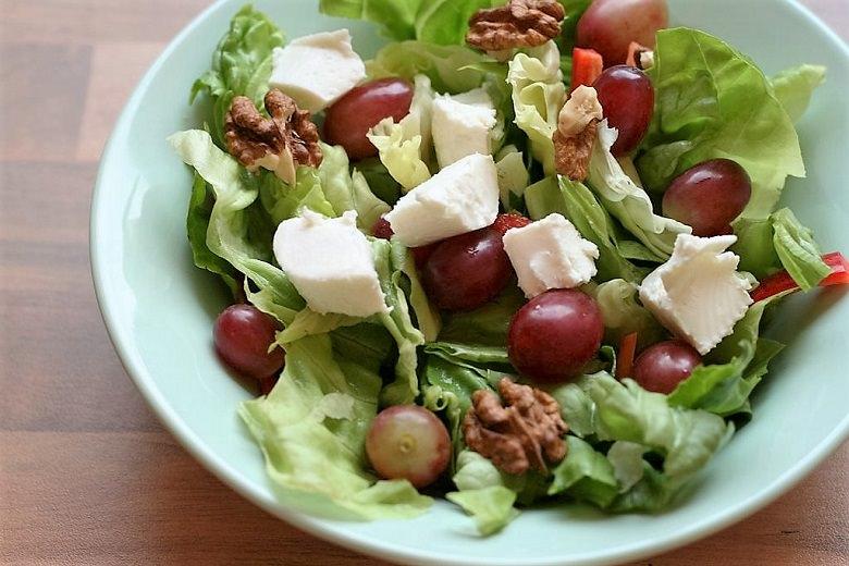Dean and David-Salat Paris in einem grünen Teller auf Holzuntergrund.