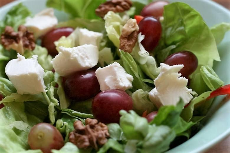 Frischer Ziegenkäsesalat mit Trauben, Walnüssen und Paprika in Nahaufnahme