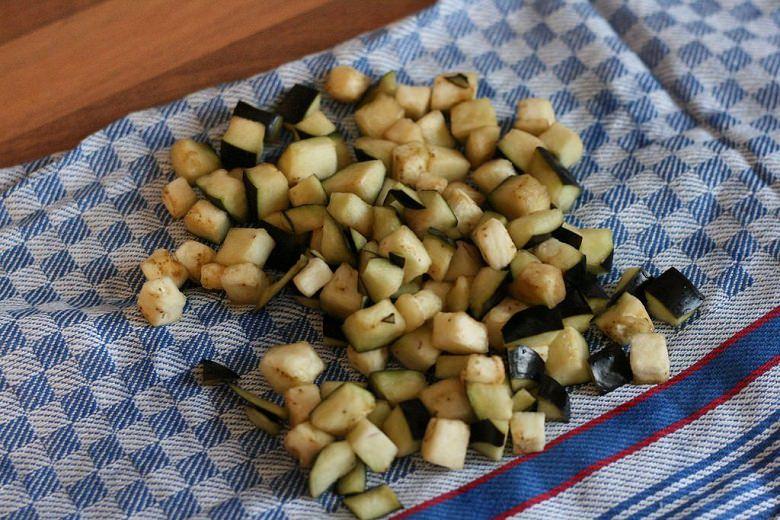 Tomaten-Aubergine-Nudeln: Auberginenstückchen auf einem Geschirrtuch