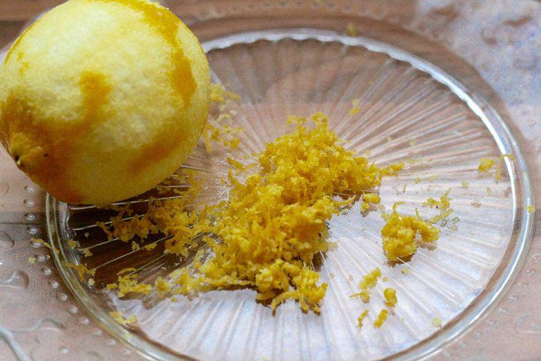 Panna Cotta ohne Gelatine - Zitronenschalenstückchen mit Zitrone auf einem Glasteller.