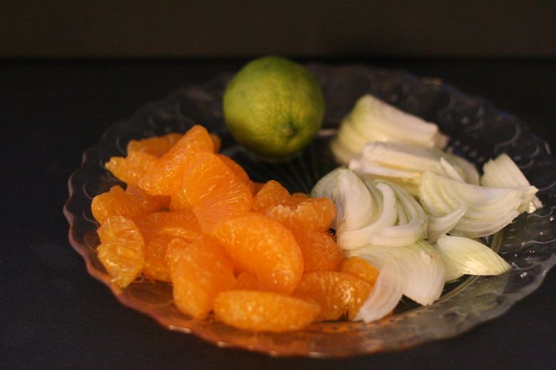 Brokkoli-Cashew Salat mit Mandarinen - Mandarinen, Zitrone und Zwiebelstreifen auf einem Glasteller.