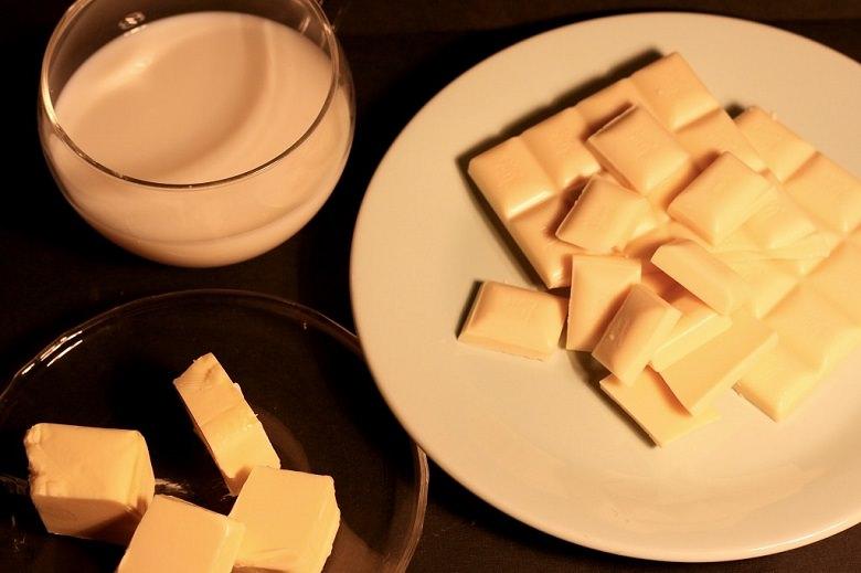 Schokoladen-Pistazien-Creme - Butter auf einer Glasschüssel, Milch im Glas und weiße Schokolade auf einem Teller.