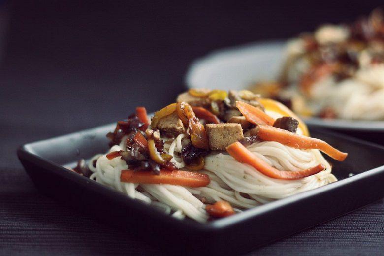Somen-Nudeln mit Gemüse auf einer Porzelanschale vor dunklem Hintergrund.