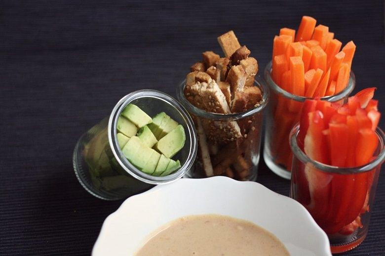 Fresh Wraps mit Avocado und Ernuss-Soße - Erdnuss-Soße in weißer Schüssel mit Karroten, Paprika, Tofu und Avocado in kleinen Gläsern.