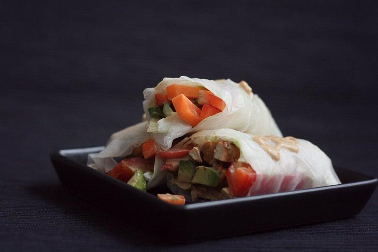 Fresh Wraps mit Avocado und Erdnuss-Soße - Fresh Wraps auf dunklem Teller.