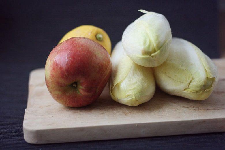 Apfel, Zitrone und drei Chicorée auf einem Holzbrett - Fruchtiger Chicorée-Salat