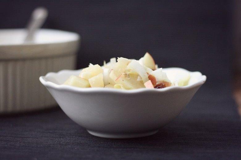 Fruchtiger Chicorée-Salat in eine weißen Schüssel vor dunklem Hintergrund.