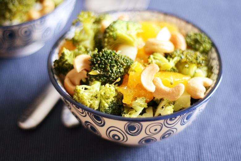 Brokkoli-Cashew-Salat mit Mandarinen - bunter Salat in einer Glasschüssel.
